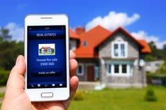 Hand die mobiele telefoon met de aanbieding van de huisverkoop houden royalty-vrije stock foto
