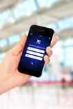 Hand die mobiele telefoon met de toepassing van het vluchtenonderzoek houden Stock Afbeeldingen