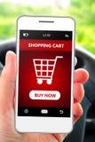 Hand die mobiele telefoon met het winkelen auto houden Royalty-vrije Stock Afbeelding