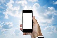 Hand die mobiele telefoon met lege ruimte op het scherm, op blauwe hemel met witte erachter wolken en helder licht houden Royalty-vrije Stock Foto