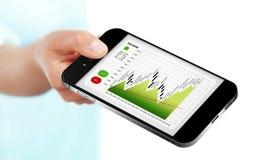 Hand die mobiele telefoon met over geïsoleerde effectenbeursgrafiek houden Stock Foto's