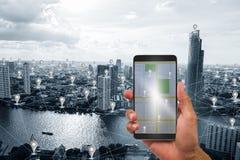 Hand die mobiele telefoon op blauwe toon slimme stad houden met het pictogram en het netwerkverbindingenachtergrond van GPS Royalty-vrije Stock Afbeeldingen