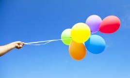 Hand die multicolored ballons houdt stock fotografie