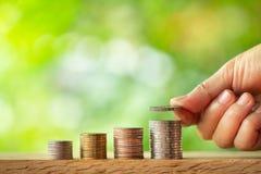 Hand die muntstuk op muntstukkenstapel zet met groen vage achtergrond stock foto