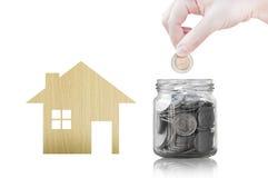 Hand die muntstuk zetten in glascontainer het kopen van een nieuw huis - besparingsgeld voor toekomstig concept Stock Foto's