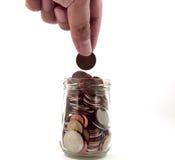 Hand die muntstukken in een glaskruik zet Stock Foto