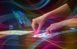 Hand die muziek op het controlemechanisme van DJ mengen met kleurrijk vibeconcept Stock Afbeelding