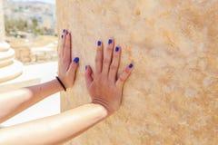 Hand die naar de granietmuur bij de oude Roman stad in Jerach, Jordanië, de zomertijd duwen Stock Foto