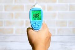 Hand, die nicht Kontaktinfrarotthermometer für Maß eine Körpertemperatur hält Gesundheitswesen und medizinisches Thema lizenzfreie stockfotografie