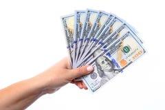 Hand die nieuwe honderd dollarsrekeningen de V.S. houdt die als een ventilator worden gevouwen, Stock Foto's