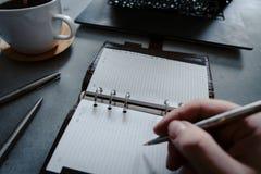 Hand die in notitieboekje met laptop als achtergrond schrijven stock fotografie
