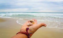 Hand, die Oberteile auf dem Strand hält Stockbild