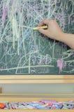 Hand die op bord met veelkleurig krijt schrijven Stock Foto