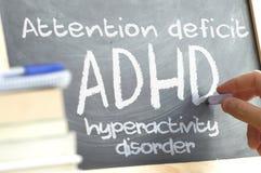 Hand die op een bord in een klasse met het geschreven woord ADHD schrijven Sommige boeken en schoolmaterialen Stock Afbeeldingen