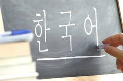 Hand die op een bord in een Koreaanse klasse met het woord & x22 schrijft; Korean& x22; schreef binnen Stock Afbeeldingen