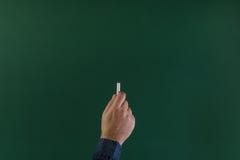Hand die op een bord met wit krijt schrijven Royalty-vrije Stock Afbeelding