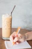 Hand die op notadocument schrijven in koffiewinkel Royalty-vrije Stock Afbeeldingen