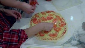 Hand die op pizzakorst gesneden tomaten wordt uitgespreid stock videobeelden