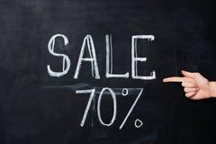 Hand die op zeventig die percentenverkoop richten op bord wordt getrokken Stock Afbeelding