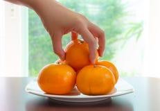 Hand, die Orange auf Teller auswählt Lizenzfreies Stockfoto