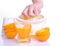 Hand, die Orange für Saft zusammendrückt Lizenzfreies Stockbild