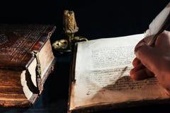 Hand die oude boekbijbel met een veer oud manuscript schrijven stock afbeelding