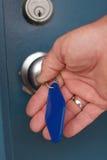 Hand die oude motelsleutel in deurslot gebruikt royalty-vrije stock fotografie