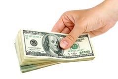 Hand die pak van $100 bankbiljetten geeft Stock Afbeeldingen