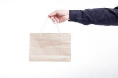 Hand, die Papiertüte auf einem weißen Hintergrund hält Stockbild