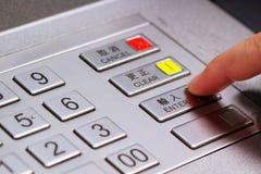 Hand die persoonlijk identificatienummer op ATM-wijzerplaatpaneel ingaan Stock Afbeeldingen