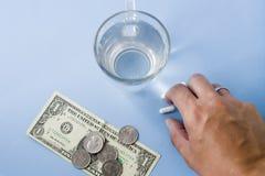Hand, die Pillen vom blauen Pastellschreibtisch, Glas Wasser, Montag nimmt lizenzfreies stockfoto