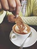 Hand, die Plätzchen mit einer Schale heißem cappunico hält lizenzfreie stockfotos