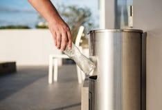 Hand die plastic flessenafval in huisvuilafval zetten stock foto