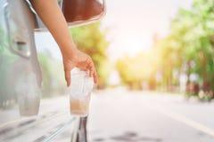 Hand, die Plastikflasche auf der Stra?e wirft lizenzfreie stockbilder