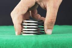 Hand, die Pokerchips auf einen Stapel setzt lizenzfreies stockfoto