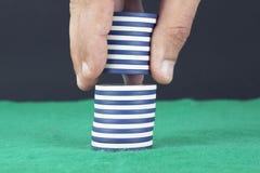 Hand, die Pokerchips auf einen Stapel setzt lizenzfreie stockbilder