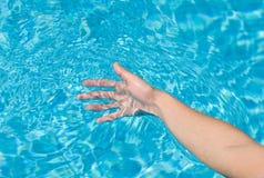 Hand, die Poolwasser spielt Lizenzfreie Stockfotografie