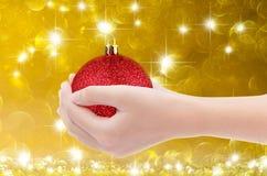 Hand die rode bal op gouden bokehachtergrond houden Stock Afbeeldingen