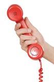Hand die rode telefoon houdt stock foto