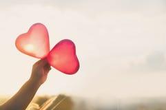 Hand, die rote Herzen über bewölktem Himmel hält Lizenzfreie Stockfotos