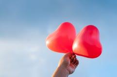 Hand, die rote Herzen über blauem Himmel hält Lizenzfreie Stockbilder