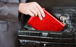Hand, die roten Organisator vom Aktenkoffer nimmt Stockfotografie