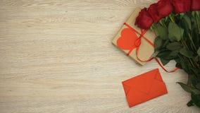 Hand, die roten Umschlag auf Holztisch nahe Bündel von Rosen und von Geschenkbox, Liebe setzt stock video footage
