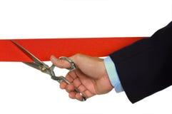 Hand, die rotes Farbband schneidet Lizenzfreie Stockbilder