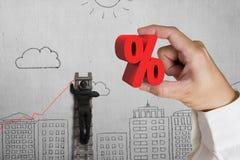 Hand, die rotes Prozentsatzzeichen mit Geschäftsmannzeichnungstendenz hält Stockbild