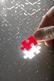 Hand, die rotes Puzzlespielstück anhält Stockbild