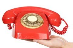 Hand, die rotes Telefon anhält stockfotografie