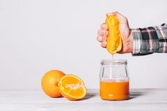 Hand die sap van een sinaasappel in een glaskruik drukken royalty-vrije stock foto's
