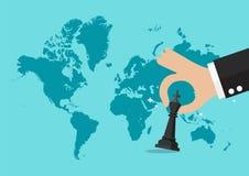 Hand, die Schachzahl mit Weltkartehintergrund hält Lizenzfreies Stockfoto