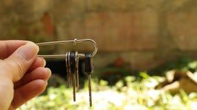 Hand, die Schlüssel in Sicherheitsnadel hält stockfotos